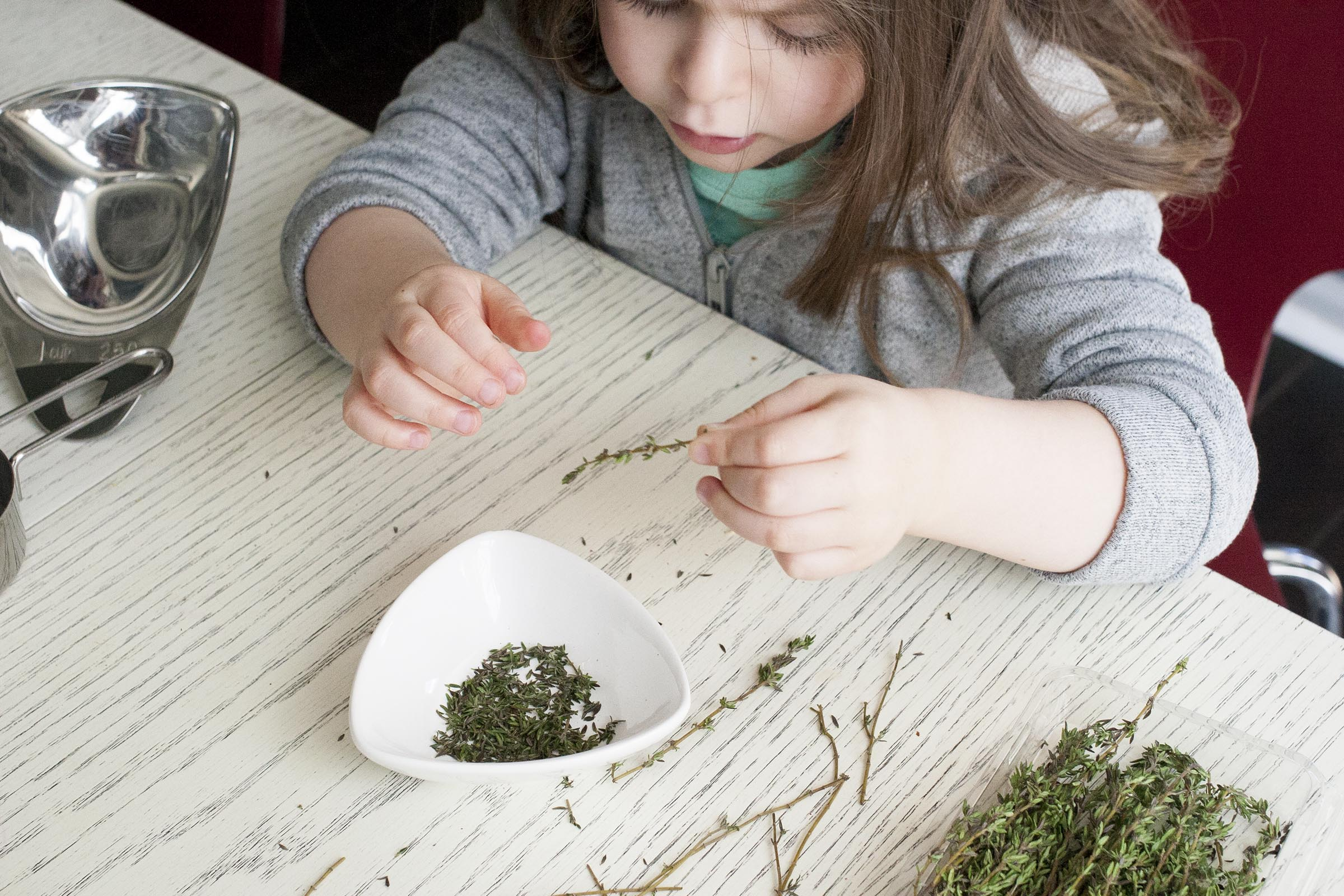 A great kid's task: plucking the leaves from a stem of thyme. www.lifeaswecookit.com